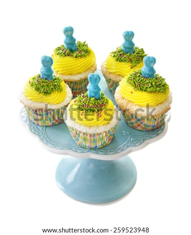 Easter cupcake. Angel food cupcake with vanilla frosting decorated with a candy bunny, isolated on white background. - stock photo