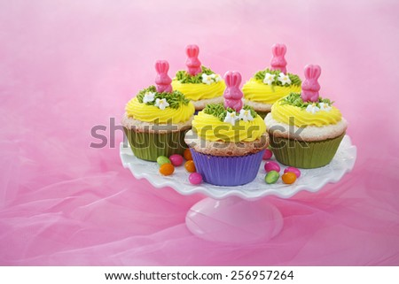 Easter cupcakes. Angel food cake with vanilla frosting and a candy bunny. - stock photo