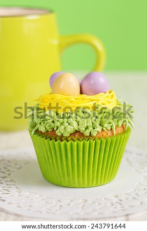 Easter cupcakes decorated with eggs in nest. Green background with coffee mug. Shallow focus - stock photo