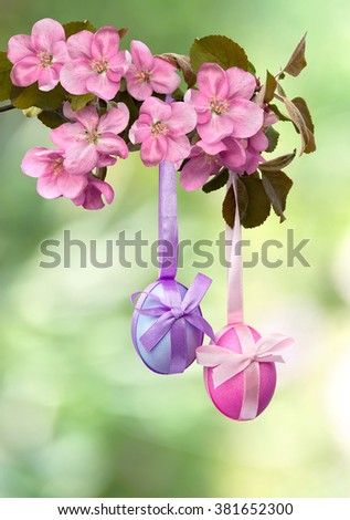 Easter decoration. Apple blossom and Easter eggs on defocused of natural background of blooming trees. - stock photo
