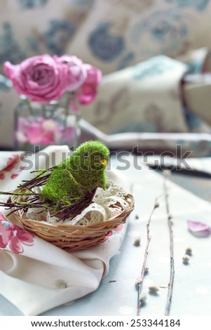 Easter decoration - bird in a nest with lace, pink roses and willow branches, natural light toned photo - stock photo