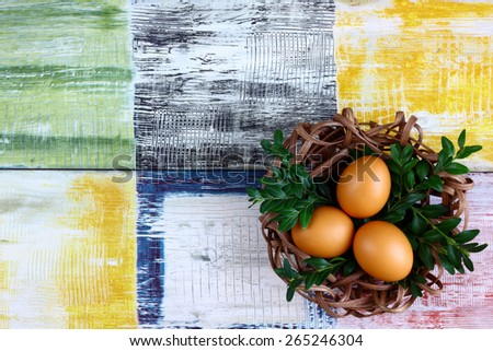 Easter decoration / card - easter fresh eggs in a nest made of rattan - pedig with boxwood twigs on wooden colorful background - space for text - stock photo