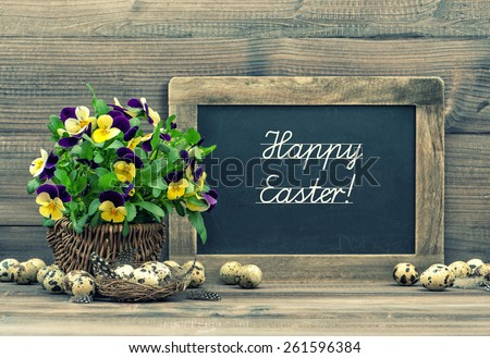 Easter decoration eggs, pansy flowers and vintage blackboard with sample text Happy Easter! Retro style toned picture - stock photo