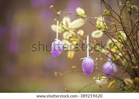 Easter decoration  in the garden. Spring bouquet of blossoming willow with easter eggs. - stock photo