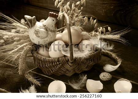 easter decoration of hen figurine in wicker basket with eggs on wooden background in vintage style - stock photo