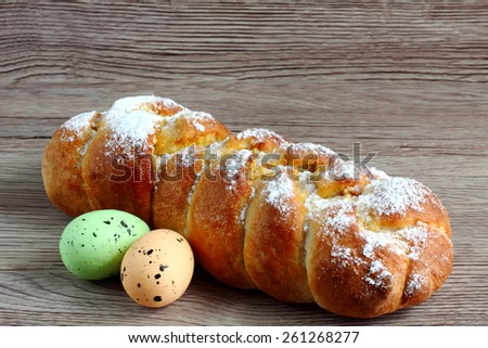 Easter decoration - sweet braided homemade bread with two easter eggs on wooden background - easter time - with space for text