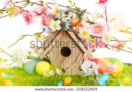 Easter decoration with birdhouse and eggs on green grass. Spring apple and cherry blossoms. Retro style toned picture with light leaks. - stock photo