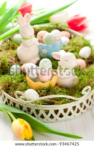 Easter decoration with bunny and chocolate eggs on moss - stock photo