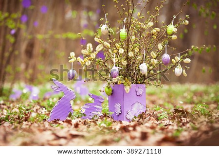 Easter decoration with easter rabbit and eggs in the garden. Spring bouquet of blossoming willow in lilac vase. - stock photo