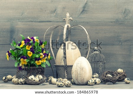easter decoration with eggs, pansy flowers, nest and birdcage. vintage style toned picture - stock photo