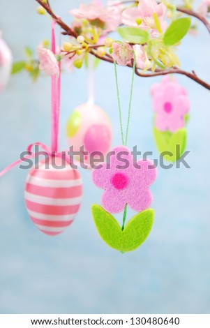 easter decoration with hanging on cherry branch painted eggs and felt flowers - stock photo