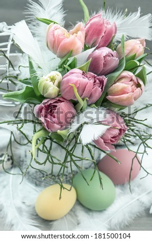 easter decoration with pink tulip flowers and colored eggs. springtime. retro style toned picture - stock photo