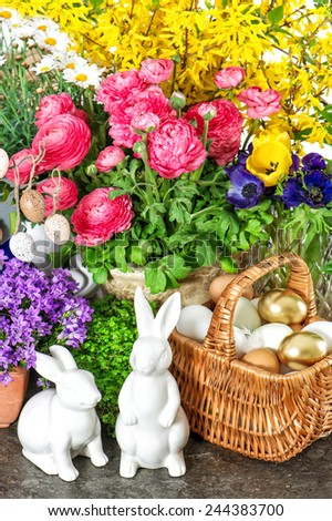 Easter decoration with spring flowers, golden eggs and bunnies. Forsythia and ranunculus blossoming - stock photo