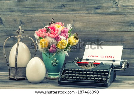 Easter decoration with tulips, eggs and antique typewriter. Sample text Happy Easter! in german. Vintage style toned picture - stock photo