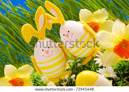 easter decoration with two eggs in bunny shape standing in grass - stock photo