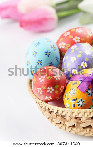 Easter decorations - flowers, basket with painted eggs on white - stock photo