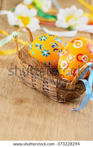 Easter decorations - flowers, basket with painted eggs on wooden table - stock photo