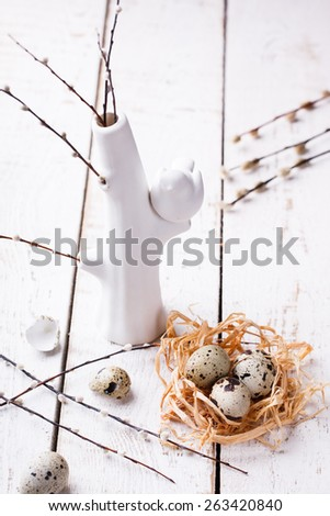 Easter decorations. Quail eggs in the nest, decorated with willow. - stock photo