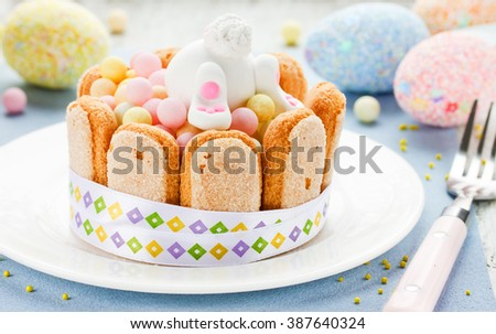 Easter dessert for children: colorful candy treats with cookies and fondant white bunny selective focus - stock photo