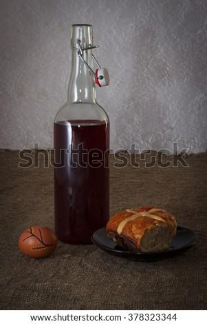 Easter dinner served on burlap tablecloth. Bottle of wine, hot cross bun, and egg.  - stock photo