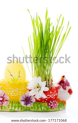 Easter egg and green grass in a multicolor holder - stock photo