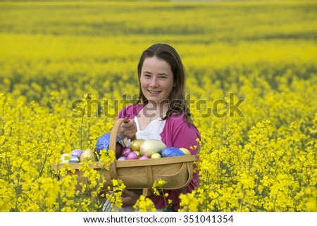 Easter egg hunt Young girl with chocolate eggs and Spring flowers