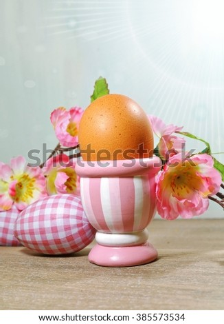 Easter  egg in a cup on a old wooden board on a background of Easter composition