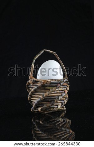 easter egg in paper basket isolated in black