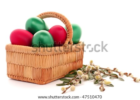 Easter egg in wicker basket and willow on white