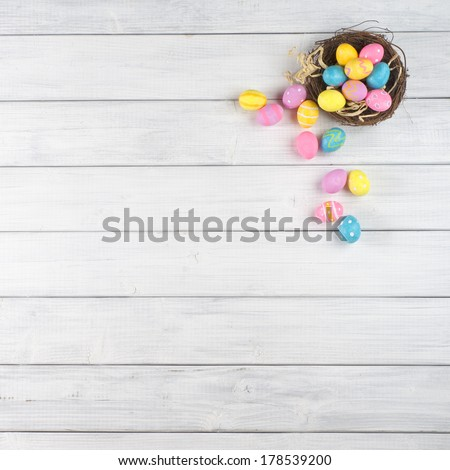 Easter Egg Nest Overflowing from Up Above with Extra White or Gray Wood Board Background for room or space for copy, text, words.   - stock photo