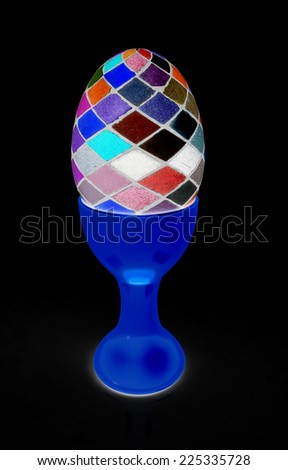 Easter egg on gold egg cups on a black background - stock photo