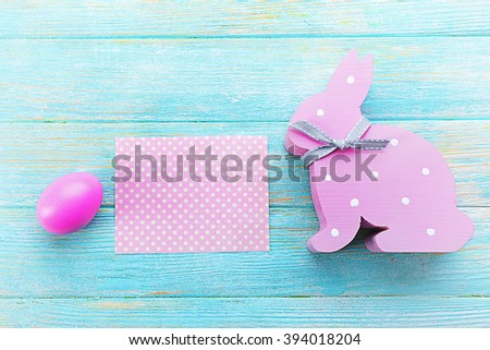 Easter egg with greeting card and rabbit on blue wooden background - stock photo