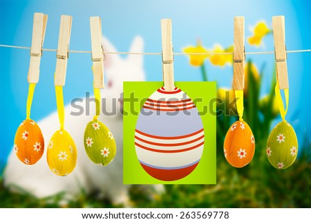 easter eggs against white fluffy bunny sitting beside daffodils with easter eggs - stock photo