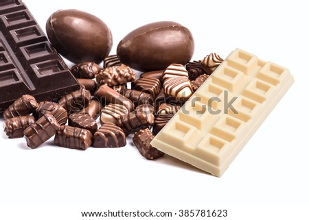 Easter eggs and assorted chocolate on white background