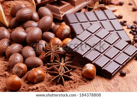 Easter eggs and assorted chocolate on wooden table - stock photo