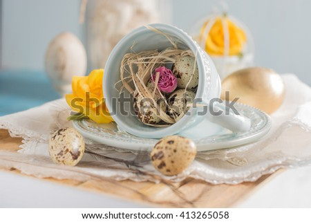 Easter eggs and chocolate hand made candies in a cup closeup on the  white napkin, Vintage aqua blue wooden background, shallow focus.