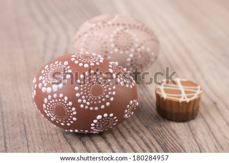 Easter eggs and chocolate praline on wooden table
