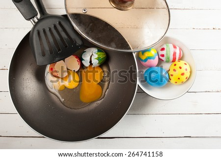 easter eggs and frying pan on wood - stock photo