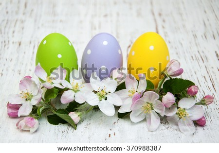 Easter eggs and spring apple blossom on a old wooden background