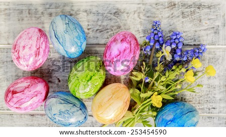 Easter eggs and spring flowers on wooden background - stock photo