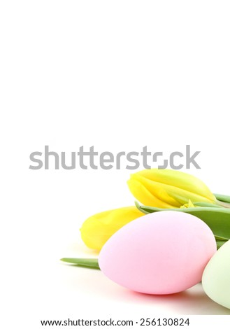 Easter eggs and tulip flowers over a white background. - stock photo