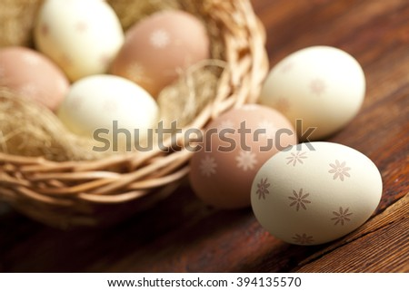 Easter eggs and wicker basket on wooden table - stock photo