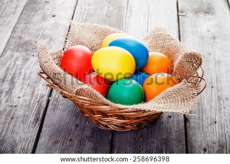 Easter eggs are lying in decorative nest inside braided basket on wooden background.  Left side is designed for text