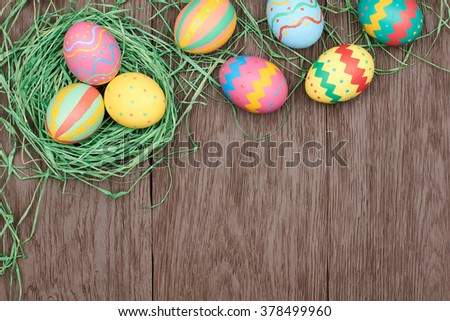 Easter eggs background. Hand painted multicolored decorated eggs on green straw nest, wood, copyspace. Unusual creative holiday greeting card  - stock photo