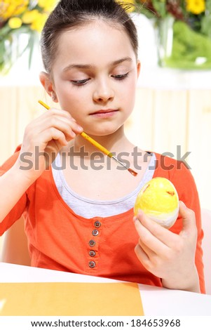 Easter eggs .Cute girl decorates decorating Easter eggs