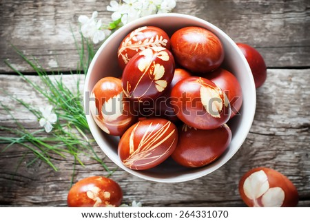 Easter Eggs Decorated with Natural Fresh Leaves and Boiled in Onions Peels, top view - stock photo
