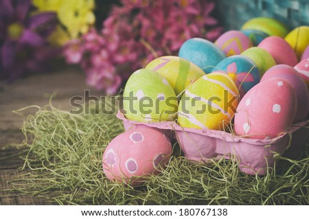 Easter Eggs Dyed by Kids in Rustic Still Life with Colorful Spring Flowers in Bokeh, with background room or space for copy, text, words.  Horizontal with vintage camera instagram treatment - stock photo