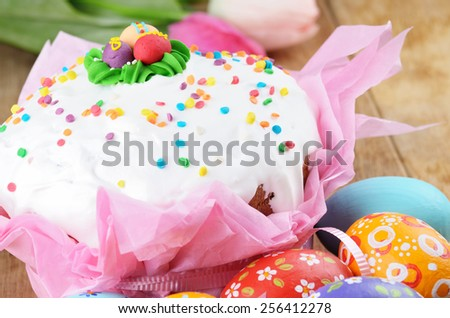 Easter eggs, flowers and cakes on the wooden table - stock photo