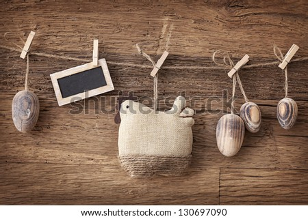 Easter eggs hanging on wooden background - stock photo