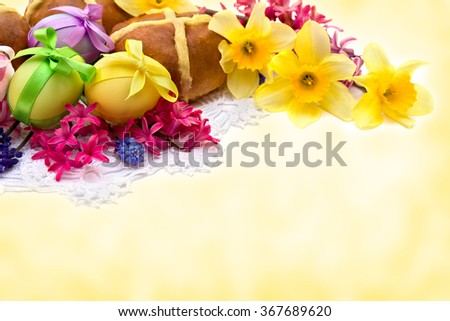 Easter eggs, hot cross bun, narcissus and hyacinth on abstract background with space for text. - stock photo